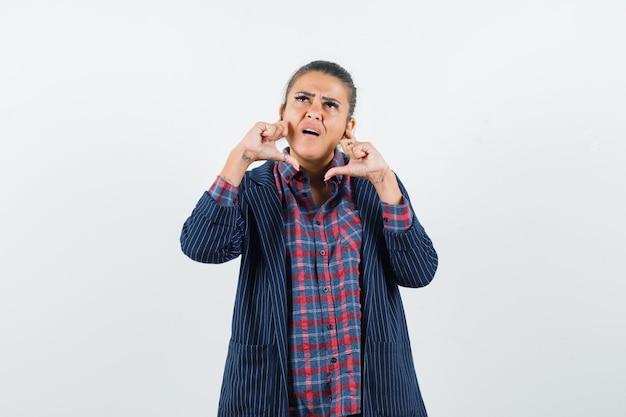 Signora che tiene le dita sulle guance in camicia, giacca e guardando pensieroso. vista frontale.