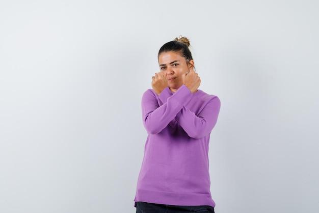拳を持った女性がウールのブラウスで交差し、自信を持って見える