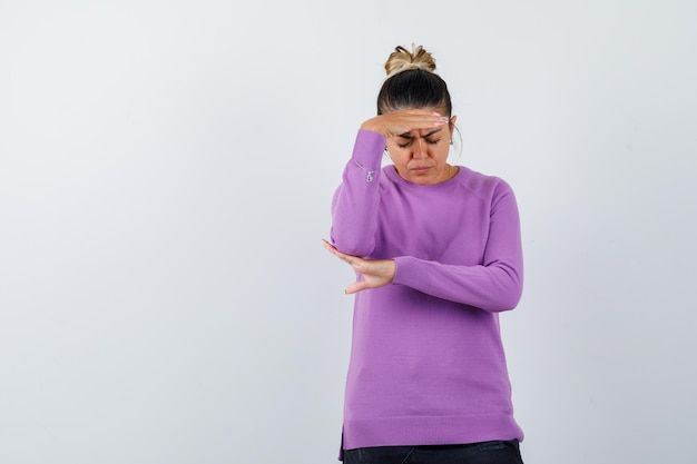 Lady holding hand over head while thinking in wool blouse and looking sad