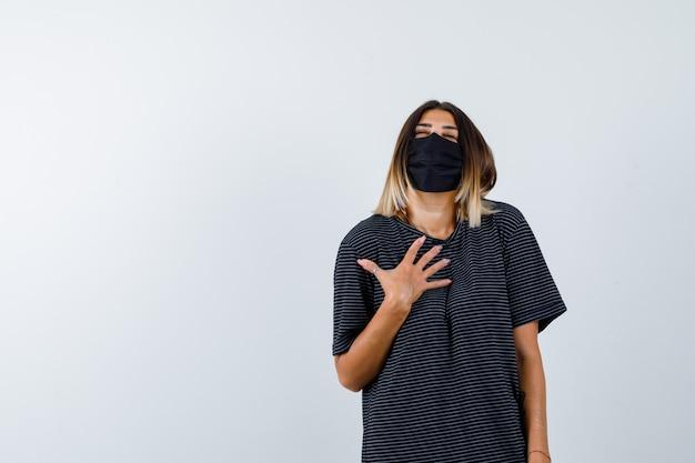 Леди, держащая руку на груди в черном платье, медицинской маске и благодарная, вид спереди.