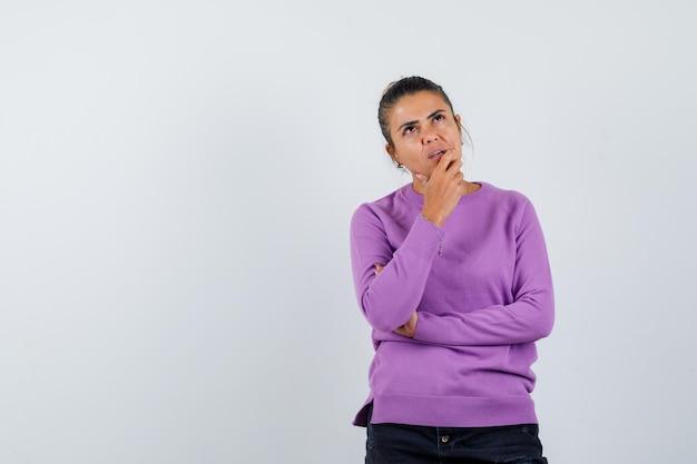 Дама в шерстяной блузке держит руку на подбородке и задумчиво смотрит
