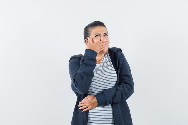 Tシャツで口に手をつないでいる女性