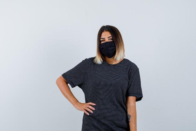 Signora che tiene la mano sulla vita in abito nero, maschera medica e sembra allegra. vista frontale.