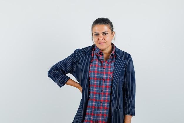 Signora che tiene la mano sulla vita in camicia, giacca e sembra sensibile, vista frontale.
