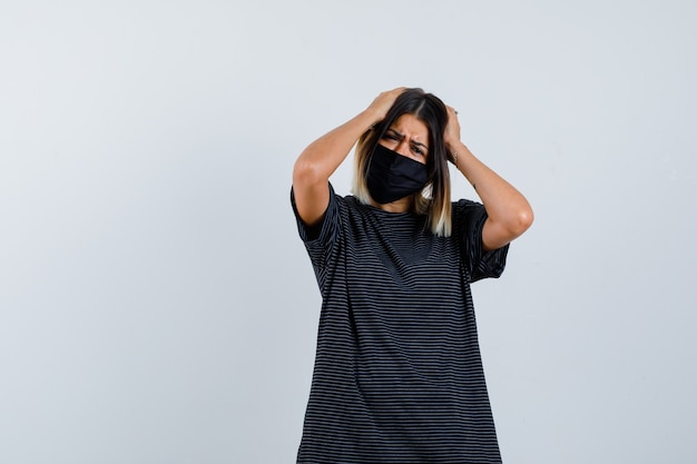 Signora che tiene le mani sulla testa in abito nero, mascherina medica e sembra angosciata. vista frontale.