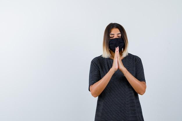 黒のドレス、医療マスクで祈りのジェスチャーで手をつないで、希望に満ちた女性。正面図。