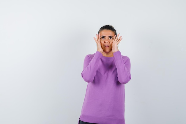 Дама в шерстяной блузке держит руки за лицо и смотрит сосредоточенно