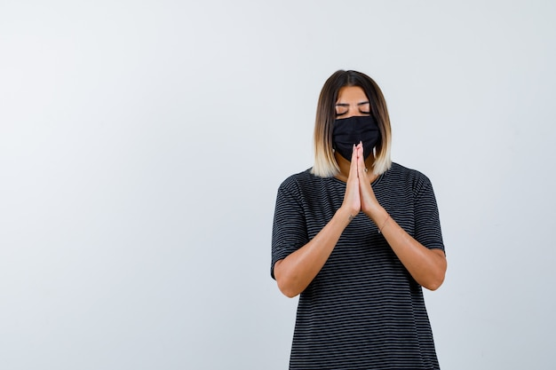Lady holding hands in praying gesture in black dress, medical mask and looking hopeful. front view.