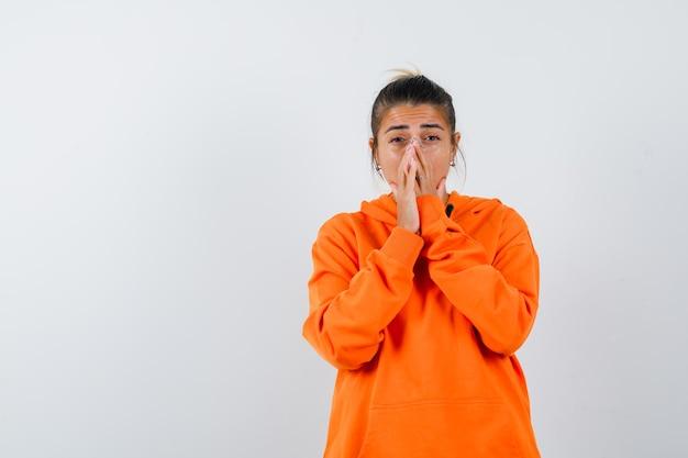 Signora che si tiene per mano in gesto di preghiera in felpa con cappuccio arancione e sembra speranzosa