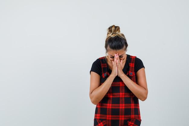Signora che si tiene per mano nel gesto di preghiera in abito scamiciato e sembra speranzosa. vista frontale.