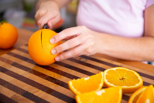 Lady holding knife and cutting orange on wooden board