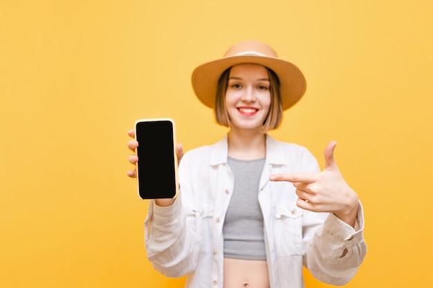 Дама держит в руке смартфон с черным экраном и показывает пальцем на нее, смотрит в камеру и улыбается