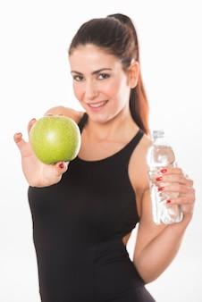 여자는 물과 사과 병을 보유