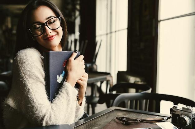 女性はカフェに座って優しい古いphotoalbumsを保持しています