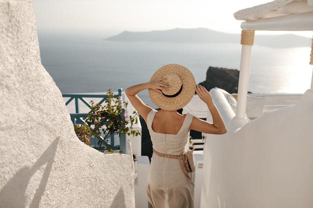 女性は麦わら帽子をかぶっています。バッグとベージュのドレスを着た女性が海に降りる