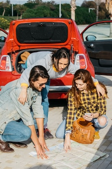 Lady hugging woman with backpack and smartphone near man and looking at map near car