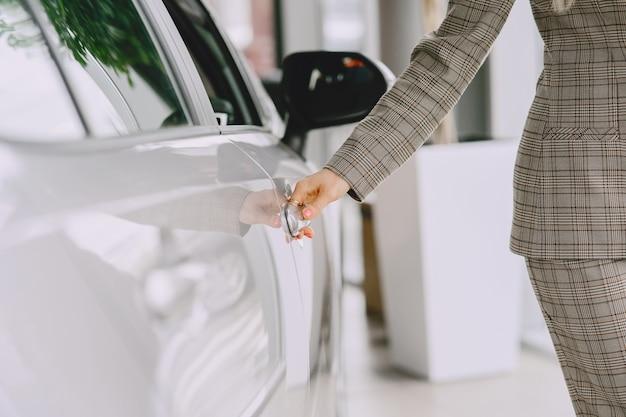 Дама в салоне автомобиля. женщина покупает машину. элегантная женщина в коричневом костюме.