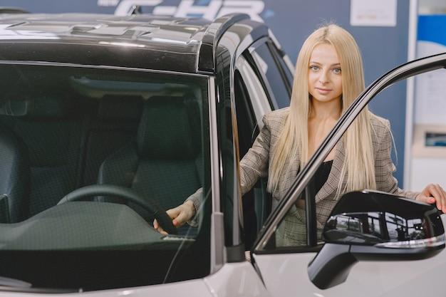 자동차 살롱에서 레이디. 차를 사는 여자. 갈색 정장에 우아한 여자입니다.