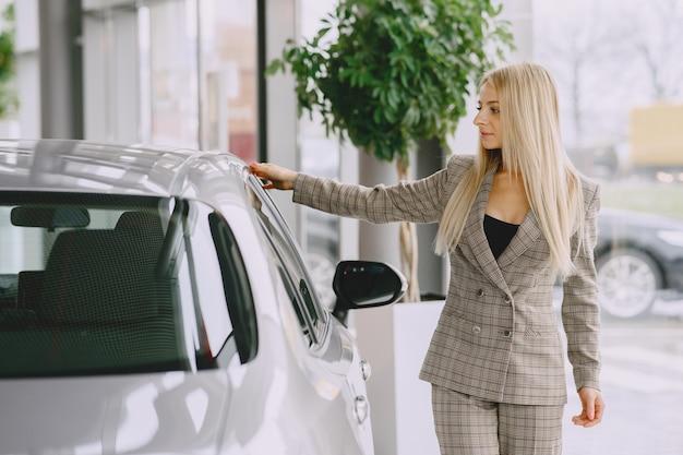 カーサロンの女性。車を買う女性。茶色のスーツを着たエレガントな女性。