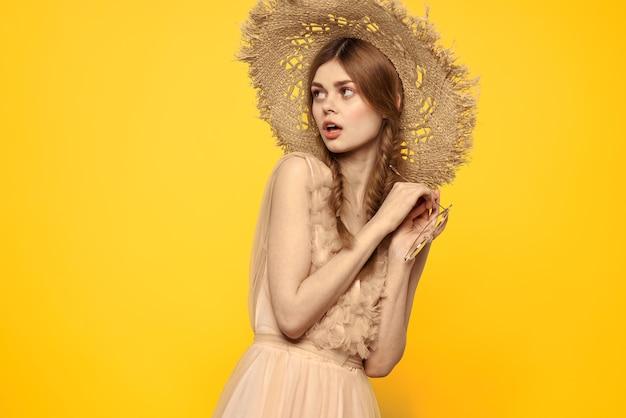 Дама в шляпе и платье красные волосы желтый фон модель портрет весело. фото высокого качества