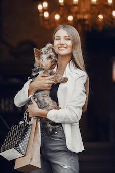 쇼핑에있는 여자. 귀여운 강아지와 여자입니다. 쇼핑 가방을 가진 여자입니다.