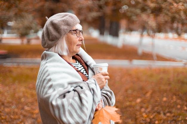 暖かいウールの毛布を着た女性は、楽しんでいる間、熱いお茶やコーヒーの紙コップを持っています