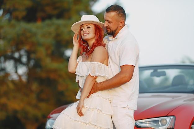白いドレスと帽子の女性。白いtシャツを着た男。森の中の人々。