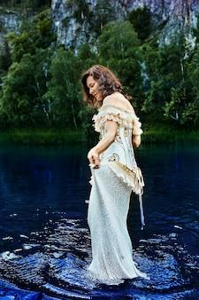 Дама в вечернем или свадебном платье с вышивкой гуляет вечером по голубой речной воде на фоне дикой природы.