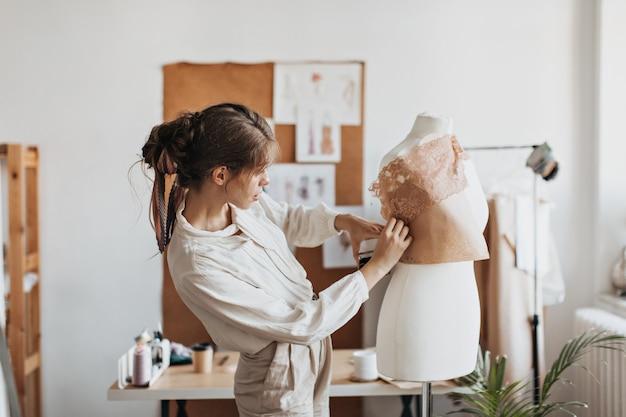 ベージュの服の女性は服のパターンをデザインします
