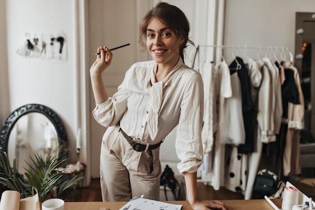 Дама в бежевом наряде позирует на рабочем месте