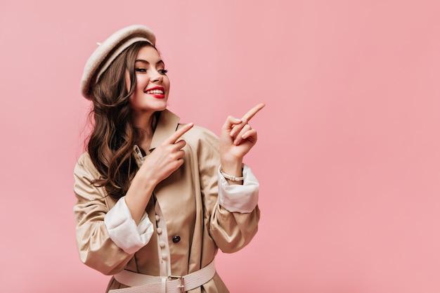 Дама в бежевом плаще улыбается и указывает пальцами на розовый фон с пространством для текста.