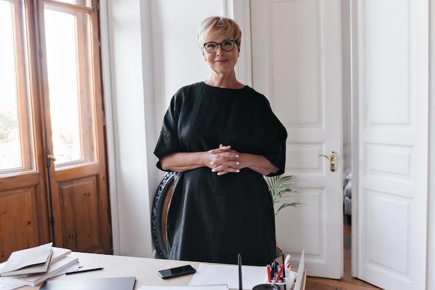 Дама в черном платье и очках смотрит в камеру в офисе