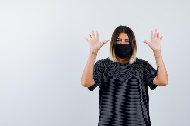 黒のドレスを着た女性、降伏のジェスチャーで手のひらを示し、自信を持って見える医療マスク、正面図。