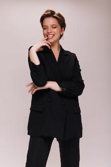 黒のスーツを着た女性が白い背景で楽しくポーズをとる。孤立したに微笑んで暗いジャケットとパンツの陽気な女性