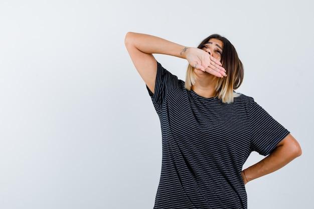 あくびをしながらリラックスした表情で口に手を当てている黒いtシャツの女性、正面図。