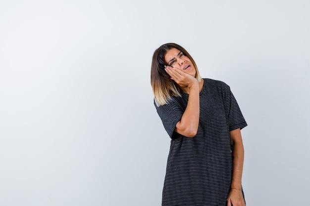 上げられた手のひらに頬を傾けて躊躇している黒いtシャツの女性、正面図。