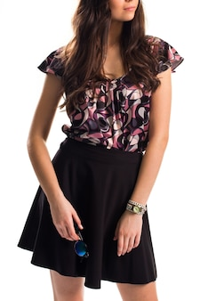 Дама в блузке держит солнцезащитные очки. черная юбка и блузка с принтом. круглые солнцезащитные очки и маленькие часы. шелковая одежда высокого качества.