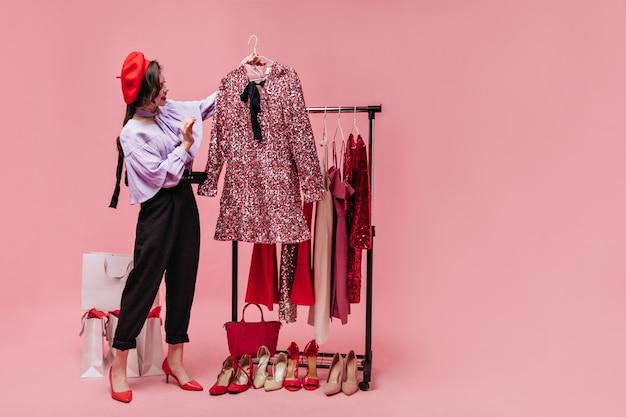 주름 장식과 빨간 베레모가 달린 블라우스를 입은 숙녀가 우아한 반짝이는 핑크색 드레스를보고 있습니다.