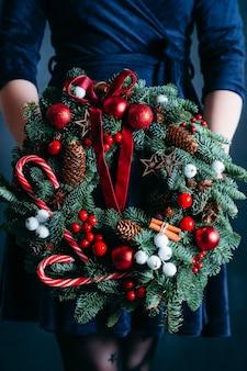 지팡이와 크리스마스 화 환을 들고 파란 드레스에 아가씨.