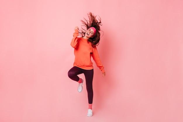 明るいスウェットシャツと茶色のレギンスの女性がピンクの壁に向かって踊る