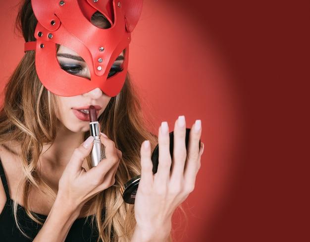 고양이 가면을 쓴 여자. 아름 다운 섹시 한 금발의 패션 초상화입니다. 빨간 고양이 마스크를 쓰고 어두운 빨간 립스틱을 바르고 있는 섹시한 여성은 빨간 배경에 고립되어 매우 관능적으로 보입니다. 아름다움과 메이크업의 개념