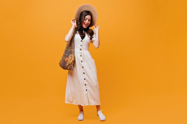 綿のミディドレスとスニーカーを身に着けた女性は、つばの広い麦わら帽子をかぶっています。オレンジ色の背景に買い物袋でポーズをとるブルネットの女性。