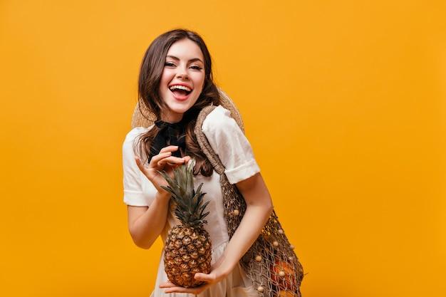 Дама в хлопковом летнем платье смеется и позирует с ананасом и эко-сумкой на оранжевом фоне.