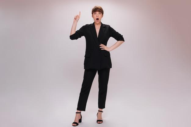 검은 양복에 레이디는 고립 된 배경에 아이디어와 놀란 포즈가 있습니다. 검은 바지와 재킷에 매력적인 여자는 흰색 배경에서 위로 가리킨