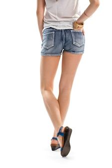 걷는 데님 반바지에 여자입니다. 흰색 탑과 파란색 샌들. 여름용 짧은 반바지. 고품질의 청바지 원단.