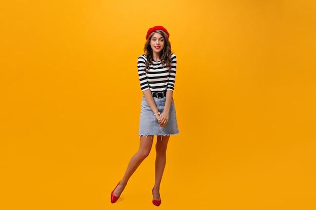 데님 스커트와 빨간 베레모 아가씨 오렌지 배경에 포즈. 유행 옷과 카메라를 찾고 밝은 발 뒤꿈치에 젊은 여자.