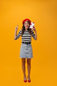 オレンジ色の背景にデニムスカートの女性のポーズ。指を交差させ、ギフトボックスを保持します。ベレー帽と明るい靴のポーズで巻き毛を持つスタイリッシュな女性。