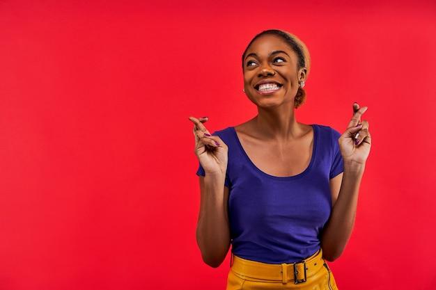 Дама в серьгах с широкой улыбкой в синей футболке стоит и скрещивает пальцы