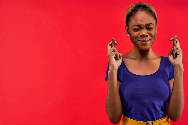 Дама в серьгах с закрытыми глазами в синей футболке стоит и скрестила пальцы
