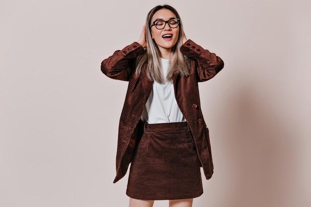 眼鏡、白いtシャツ、ベージュの壁に笑みを浮かべて茶色のスーツの女性